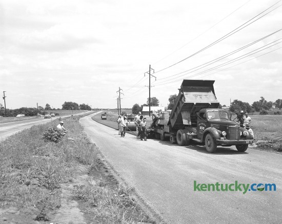 Workers pour the first of three courses of blacktop on a new section of New Circle Road in June of 1958. This section was to be four lanes from west of Newtown Pike to a point near North Limestone Street.