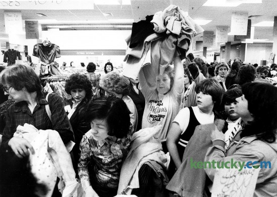 When the crowd at Lexington Malls' McAlpin's hollered during a moonlight madness sale for more clothes at discount prices of $1 and $2, Lolene Dawkins came to the rescue April 10, 1984. She would take clothes from another table and throw them over the heads of unsuspecting shoppers.  Photo by Steven R. Nickerson | Herald-Leader staff