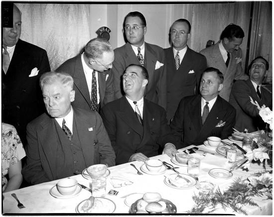 Above, the Lexington Co-Operative Club held a testimonial dinner to U.S. Sen. A.B. (Happy) Chandler in April 1945 at the Lafayette Hotel. Chandler was being honored as the newly appointed commissioner of major league baseball. Chandler is seated at the center of the table, turning his head to speak to a man standing behind him. Seated at right, next to Chandler, is Adolph Abraham, president of the Co-Operative Club. Standing, from center to left, are William E. Benswanger, president of the Pittsburgh Pirates; William DeWitt, general manager of the St. Louis Browns; and Earl Hilligan, representing Will Harridge, president of the American League. The identities of the other men in the photo are unknown.Chandler was twice governor of Kentucky and served in the U.S. Senate. He resigned his Senate seat to become the second commissioner of baseball. During his tenure, from 1945 to 1951, he approved Jackie Robinson's contract with the Brooklyn Dodgers, helping to integrate baseball, and he established the first pension fund for players. Owners became upset with Chandler and did not renew his contract.