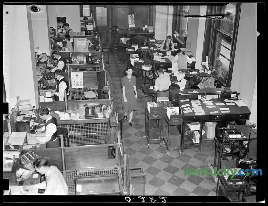 """First National Bank and Trust Company founded April 1, 1865 celebrated their 75th anniversary on March 31,1940 with a special ceremony held at the bank.  To promote the anniversary the Leader published this photograph showing an informal view of """"behind the scenes"""" at the First National Bank and Trust Company which showed the interior of the tellers' cages at the left, and a battery of desks, files and computing machines manned by busy clerks and auditors at the right.  Published in the Lexington Leader March 31, 1940. Herald-Leader Archive Photo"""