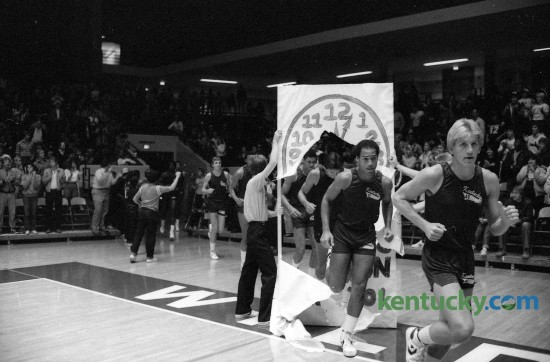 "The University of Kentucky's first ""Midnight Practice"", later called Midnight Madness, occurred October 14, 1982 in Memorial Coliseum. Troy McKinley, right, and Derrick Hord led the way through a paper banner that read ""The Cats will Run at 12:01."" Photo by E. Martin Jessee 