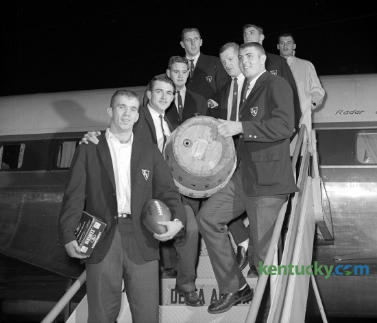 The Kentucky Wildcats arrived at Blue Grass Field Nov. 24, 1962 with the trophies of their 12-10 victory at Tennessee -  the game football and the Beer Barrel. The Beer Barrel would go to the winner of the annual game between the SEC schools. The blue and orange barrel resided at the home of the winning team from 1925 until 1998, when it was discontinued after an alcohol-related car crash involving Kentucky players. At the time it was retired, the barrel had been in UT's possession since 1985. The players in the picture are, left row, bottom to top, Clarkie Mayfield, whose two field goals decided the game; Darrell Cox, who scored Kentucky's lone touchdown; Ray Heffington and Frank Sakal; right row, bottom to top, Herschel Turner, holding the beer barrel, Jim Hill, Jim Komara and Jerry Woolum.