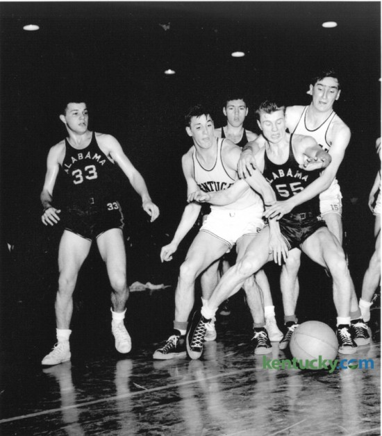 "University of Kentucky's Alex Groza, center left and Wallace ""Wah Wah"" Jones, right, battled Alabama's Carl Shaeffer (55) for a loose ball in Alumni gymnasium February 16, 1948. The other Alabama players are not identified. UK won 63-33. That year's UK team, coached by Adolph Rupp, finished the season as World Champions (Olympic Games); National Champions; SEC Champions and SEC Tournament Champions. Leading scorers were Alex Groza, 12.5 ppg; Ralph Beard, 12.5 ppg; Wallace Jones, 9.3 ppg; James Line, 6.9 ppg; and Kenneth Rollins, 6.6 ppg."