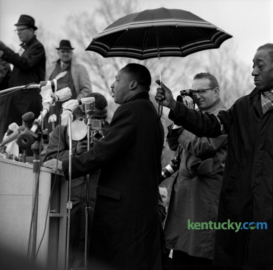 The Rev. Dr. Martin Luther King, was sheltered by an umbrella from the rain as he addressed some 10,000 people who attended a rally in Frankfort at the State Capitol on March 5, 1964. Photographer Bill Strode, center, was on assignment for the Louisville Courier Journal.