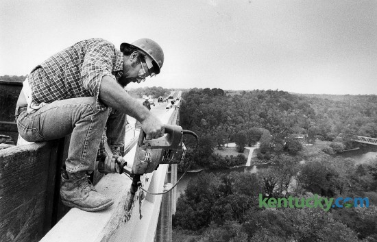 Carlos Wall has a bird's eye view of the Kentucky River as he uses an electronic chipping hammer on the Interstate 75 bridge at Clays Ferry Oct. 4, 1983. The northbound lanes were being repaired and in this case, one lane was not open as Wall was removing some bulging concrete from the wall. Photo by Charles Bertram | staff