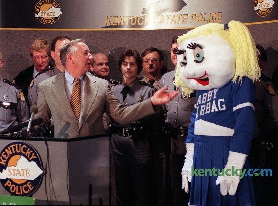 """Jerry Lovett introduces mascot """"Abby Airbag"""" during airbag an safety awareness press conference Feb. 11, 1997 in Frankfort. Kentucky State Police – along with the Chrysler Corp., the American Automobile Association and the American Academy of Pediatrics – unveiled a public education campaign that children should sit buckled up in the back seat when they ride in vehicles equipped with air bags. Abby Airbag,"""" a safety mascot dressed in a Kentucky blue and white cheerleader skirt and saddle shoes, will help spread the message at schools and day care centers. Tina Cox, program manager with the Kentucky State Police Highway Safety Standards Branch, came up with the idea for """"Abby Airbag"""" while taking a shower one morning before work. Cox's husband Rusty, who is a firefighter, put his wife's thoughts on paper and the sketch was sent to a West Virginia company that makes mascots for colleges and universities. One month and $1,600 later and Kentucky has its own spokesperson to spread the word about air bag safety. Photo by Mary Annette Pember 