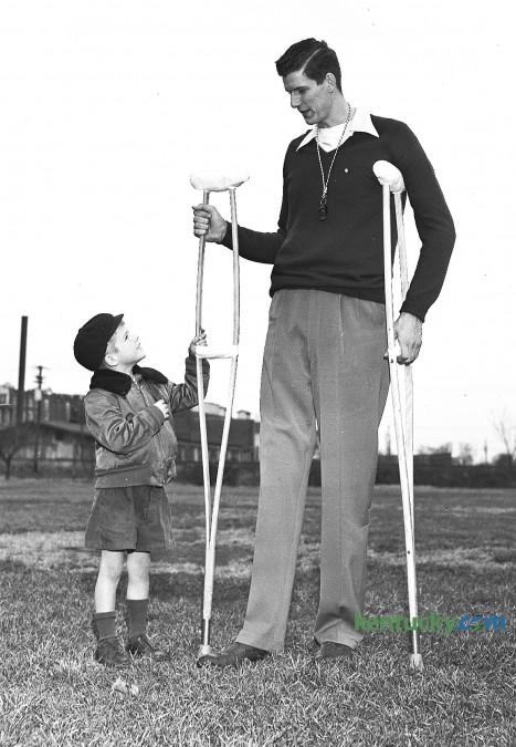 Six-year-old Ellis Harfford Jr. has a look at University of Kentucky basketball player Bill Spivey's cruthces, Nov. 13, 1951. The Wildcats All-American center underwent a knee operation three weeks prior to this photo. Spivey, UK's first 7-foot-tall player, had dreams of playing for the National Basketball Association, but those dreams were dashed after he was implicated in a point-shaving scandal in the early 1950s. Several current and former UK Wildcats of the era admitted they accepted money to shave points. But Spivey, who was indicted for perjury in the case, was adamant to the end of his life that he never had any part in attempts to fix college games. A New York trial jury voted 9-3 for acquittal, and the district attorney's office said it saw no use in trying the case again. But the damage was done. Although Spivey was never found guilty of any wrongdoing, he was barred from the NBA for life before he had a chance to play his first pro game. He went on to play for some minor professional teams, including a stint with a team opposing the Harlem Globetrotters. Herald-Leader archive photo