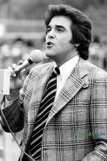 """Television personality Chuck Woolery sings """"My Old Kentucky Home"""" during halftime of the Morehead State football game Oct. 15, 1977 in Morehead. Woolery, a Morehead State alumnus, was the original host for the game show Wheel of Fortune. He also hosted (more than 2,000 episodes) Love Connection, Scrabble, The Home and Family Show, The Chuck Woolery Show, The Dating Game, Greed and Lingo. Woolery who was born in Ashland, studied economics and sociology at Morehead. Photo by David Perry 
