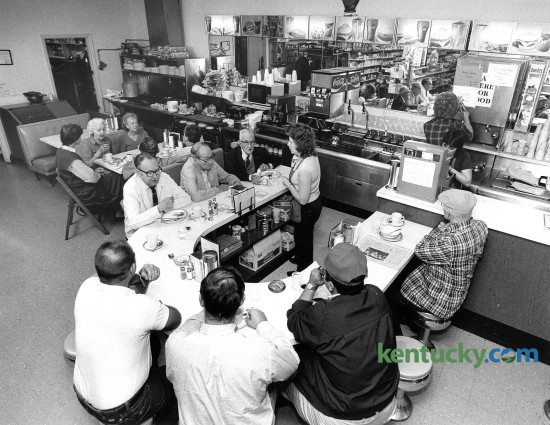 """The breakfast crowd at Wheeler Pharmacy, 336 Romany Road in Lexington, Oct. 8, 1985. A gathering spot since it opened in 1958, the drugstore serves breakfats and lunch. It has a faithful contingent of morning coffee drinkers who settle the affairs of the world and regulars including UK basketball coaches Jon Calipari and Matthew Mitchell. The lunch counter was installed by owner Buddy Wheeler as a place where people could have coffee while waiting for their prescriptions. """"At first we featured cold sandwiches and ice cream treats,"""" he said in a 2002 interview. Thanks to its popularity, """"We expanded in 1965 and doubled the size and added a grill,"""" he said. Photo by Frank Anderson 