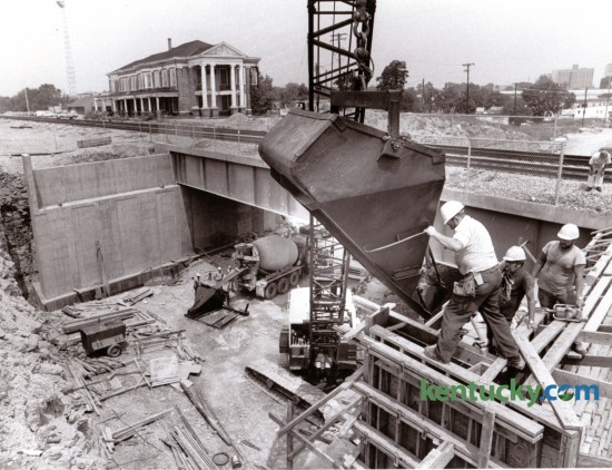 Adrian Surber, an employee of R.R. Dawson Bridge Company, Bloomfield, Ky., maneuvered a bucket holding concrete into position during construction of a bridge abutment for the South Broadway railroad underpass, August 8, 1985. Photo by David Perry | Staff