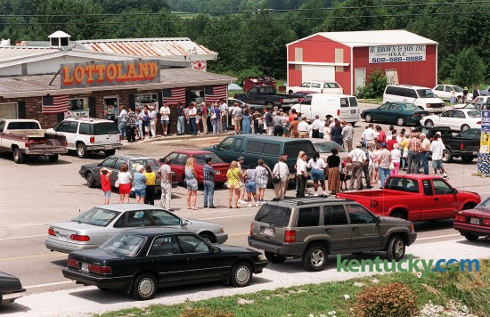 "Patrons of Lottoland stood in line July 28, 1998 in Franklin, Ky. near the Tennessee border, to buy tickets for an estimated $250 million Powerball jackpot. Store owner Don Spears said he sold $50,000 to $60,000 worth of Powerball tickets daily during this latest frenzy. From the moment the doors opened at 8 a.m. to closing time at 10 p.m., players lingered in the Lottoland parking lot, awaiting their chance to trod the worn red carpet from the front door to the lottery registers in back. Spears keept the doors locked to satisfy the fire marshal, opening it for only two dozen people at a time. When they reach the L-shaped counter with the registers, they pull out rolls of ten-, twenty- and hundred-dollar bills. ""One guy spent $8,000,"" Spears said. ""He had cash."" Kentucky Lottery spokesman Rick Redman said Lottoland, which is a quarter mile from an Interstate 65 exit just north of the Tennessee state line, is one of the biggest lottery sellers in the state. It is still open today. A group of machinists who called themselves ""The Lucky 13"" stepped forward to claim the $295.7 million Powerball jackpot - the biggest prize to that date. Photo by David Stephenson 