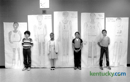Picadome Elementary students, from left, A.J. Petrucelli, Tanya Pass, Issac Coffey and Mark Patterson, posed with live-size drawings of University of Kentucky basketball players on April 3, 1984. The players, from left are, Dicky Beal, Kenny Walker, Sam Bowie, Melvin Turpin and Jim Master. Photo by Charles Bertram | Staff