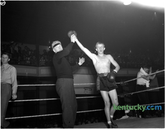 Aloft went the snappy right hand of Jimmy Barrett, lifted by referee Charley McCarthy on February 3, 1948, after the Lexington boy punched out a decision in four rounds over Archie Ware of Shelbyville to win the state open featherweight title and become the first Open champion crowned in The Herald-Leader Golden Gloves tournament at Woodland auditorium.  The featherweight king won a chance to compete in the national Golden Gloves tourney through his victories here. Published in the Lexington Leader February 4, 1948.