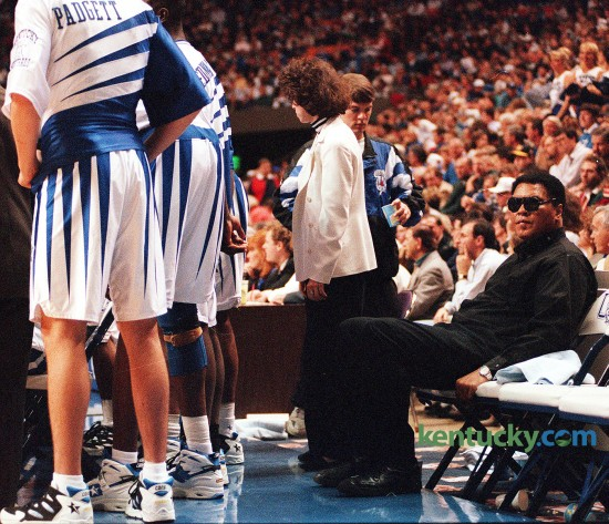 "Three-time heavyweight boxing champion Muhammad Ali sat on the Kentucky bench during the Cats' game against Florida, Feb. 18, 1995 at Rupp Arena. Ali attended the game as part of a one-day promotional visit to Lexington for a play, Ali, which ran later that month at the Opera House. A playful Ali met the UK players in the locker room before the game. ""He said I'll take you all on,"" Jeff Sheppard said. Ali also threw some punches. ""I jabbed at Anthony Epps,"" Rodrick Rhodes said. ""He told Epps he reminded him of Joe Frazier."" UK coach Rick Pitino noted that the UK players were too young to remember Ali in his fighting prime. ""For me, personally, it was a thrill of a lifetime,"" the UK coach said of Ali's presence on the bench. Ali and Sheppard shared a laugh while the game neared its dramatic finish. With 1:23 left and the Cats ahead 77-75, Sheppard was fouled but had to leave the game because of blood on his nose. Chris Harrison entered the game and made both free throws. As Harrison shot and team physician Dr. David Caborn worked on a cut on Sheppard's nose, Sheppard turned to Ali and said something. Ali and Sheppard then smiled. ""I told him I got punched in the nose,"" Sheppard said. Photo by Mark Cornelison 