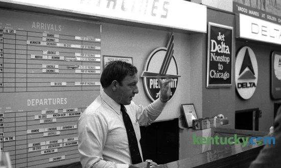 Bill Heflin, working the Piedmont Airlines ticket counter at Blue Grass Field, Dec. 9, 1974. At the time of this photo there were four major airlines that flew out of Lexington: Allegheny, Delta, Eastern and Piedmont. Looking at the arrivals and departure board behind him, the airline had service to and from Lexington to such cities as Greensboro, N.C., Norfolk, Va., Louisville and Cincinnati. Photo by Frank Anderson | staff. Published in the Lexington Herald, Dec. 10, 1974