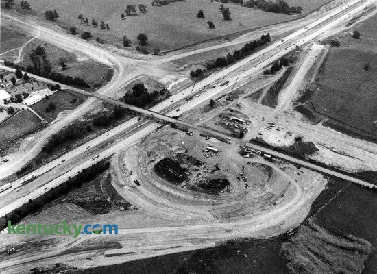 """Construction of the Man o' War Boulevard interchange with Interstate 75, June 17, 1988. I-75 runs towards the top right of the picture while what would be come Man o' War Boulevard comes into the frame from the upper left corner. Man o' War replaced Bryant Road, which shown here going over the interstate, was torn down in October 1988. Today a portion of Bryant Road exist to the west of I-75. Six months later, this last part of the Man o' War project was completed with little fanfare. Man o' War had been listed on city plans since the 1930s, but for many years, it was to be called Tiverton Way. The Urban County Council decided in 1974 that it would be named Man o' War Boulevard, after the famous race horse who never raced in Kentucky but retired to stud here. The road was completed and widened in segments over the years. The first section of road -- between Richmond Road and Palumbo Drive -- was opened in 1975. A second section opened four years later, a third four years after that. Man o' War was built by the state. It was planned, designed and will be maintained by Lexington. The state paid $37.6 million of the cost. The city paid $11 million. Along with the new I-75 interchange was a new sign on the interstate that said """"Man o' War,"""" but the sign didn't indicate that the road went to Lexington. Man o' War as since been been further extended to the east, ending at Winchester Road.  Photo by Charles Bertram 