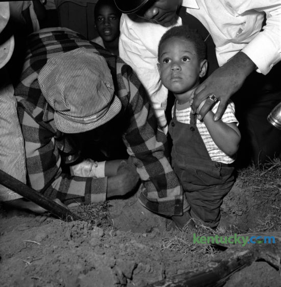 Three-year-old Calvin Doty Jr. waited to be freed after catching his foot in a post hole on October 16, 1951. Doty, son of Mr. and Mrs. Calvin Doty, Jr., 712D Charlotte Court was uninjured and excavated from the hole with the assistance of Aleza Jackson, left, and Patrolman Prather Walker.  Published in the Lexington Herald October 17, 1951. Herald-Leader Archive Photo