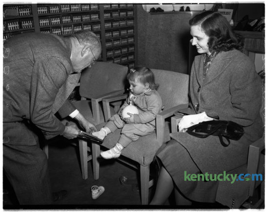 "Toddler Kathy Lewis being fitted by S.B. Foley with pair of shoes at Baynham Shoe Company, Feb. 4, 1949. The popular shoe store founded by three brothers at 135 East Main Street, operated for more then 50 years before closing in the 1970s. Their motto was ""shoes of distinction"". Around the time of this photo, they were advertising white buck shoes for men for $4.95 a pair. The site of where the store was is where Phoenix Park is."