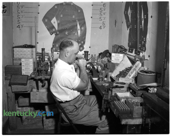 Patrolman Wallace McMurray reloading amunition in the basement of the offices of the Lexington Police Department, June 7, 1949. Under a new program, all officers go through pistol practice and to reduce cost, McMurray is responsible for melting and casting bullets and re-loading and re-priming empty cartridge cases for the officers. The equipment he is using was recently purchased to keep up with the demand of the training. Published in the Lexington Leader June 8, 1949.