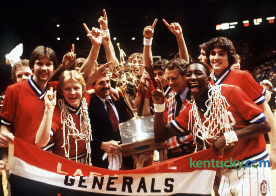 """The Lafayette Generals basketball team celebrate after winning the Boys' Sweet 16 championship, March 17, 1979 in Rupp Arena. Dirk Minniefield, who was named Mr. Basketball that year, is front right with the net around his neck. Assistant coach Donnie Harville and head coach Charles """"Jock"""" Sutherland, right, hold the trophy. On Oct. 23, 2016, Sutherland was named to the Kentucky High School Athletic Association 2017 Hall of Fame class, along with 10 others. Photo by Ron Garrison 