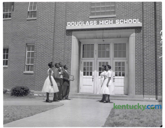"""Top honor seniors got together after the annual Award Day program at Douglass High School to admire the $200 name plaque their graduating class presented to the school at Class Night exercises on Monday May 26, 1958. Honor members of the senior class which """"did something"""" about the fact that Douglass had never had a name marker over its front doors, include, from left, Charlesanna Brown, Delta Sigma Theta sorority $100 scholarship; Randolph Stewart, salutatorian, Female Education Society $100 scholarship and Alpha Phi Alpha fraternity award; Lonny Demaree, third-honor student; James Barlow Jr., valedictorian, Watkins English Plaque; June Taylor, leader award, and Carolyn Dawson, Female Education Society $100 scholarship. The name plaque was installed with neon lighting. Herald-Leader Archive Photo"""