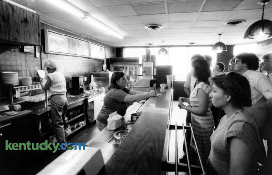 Ellen Johnson, center, took orders at the counter of Lexington's Tolly-Ho restaurant, on the last day at its original location, Mat 11, 1985. The popular campus hangout near the University of Kentucky, has been a Lexington institution since 1971 when they opened at their first location at what was then 108 W. Euclid, today known as Winslow St. In March of 1985, the 24-hour greasy spoon couldn't make a deal for a new lease and relocated in August 1987 around the corner at 395 S. Limestone. They rented there until in May 2011 when they opened at their current location, purchasing the empty Hart's Dry Cleaning building at 606 South Broadway. At the original location shown here, they sold two eggs and toast and jelly for 99 cents. But a quarter-pound hamburger, known as a Tolly, outsold everything else on the menu 10 to 1. Photo by J.D. VanHoose | staff