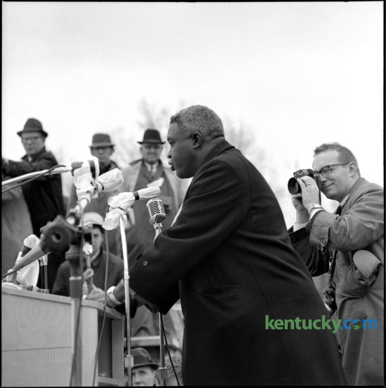 "Former Brooklyn Dodgers ballplayer Jackie Robinson addressed a crowd of 10,000 at a civil rights rally at the state capitol in Frankfort, March 5, 1964. Dr. Martin Luther King Jr. and other civil rights leaders led the peaceful demonstration, calling for a ""good public accommodations bill"" to prohibit segregation and discrimination in stores, restaurants, theaters and businesses. At right is photographer Bill Strode, who was on assignment for the Louisville Courier Journal. Herald-Leader Archive photo"