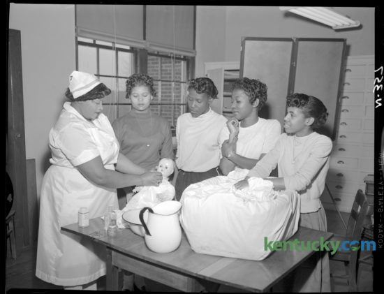 Baby-care techniques were demonstrated by Mrs. Fannie Foster, left, a licensed practical nurse and Red Cross nurse instructor,  to members of a Red Cross home-care of the sick class at Douglass High School in February 1957. Watching are, from left, Loretta Beatty, Charles Anna Brown, Delores Edwards and Carolyn Jackson. They were among 15 junior and senior home economics students enrolled in the class, which met for a total of 15 hours. Herald-Leader Archive Photo